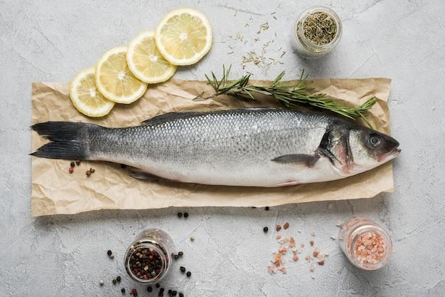 Плоская кладка рыбы с зеленью и лимоном