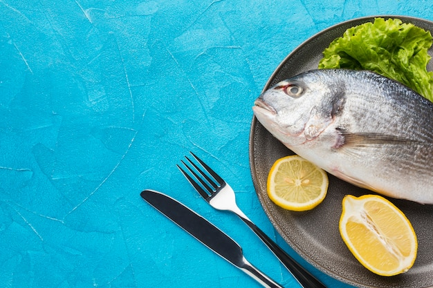 Flat lay fish with lemon on plate