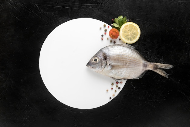 Flat lay of fish with plate and lemon