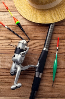 Flat lay of fishing essentials with hat and rod