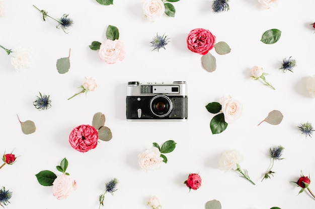 Flat lay floral frame with vintage retro camera, red and beige rose flower buds pattern on white background