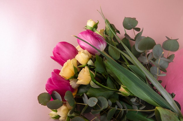 Flat lay flower arrangement with roses and tulips on a pink background top view