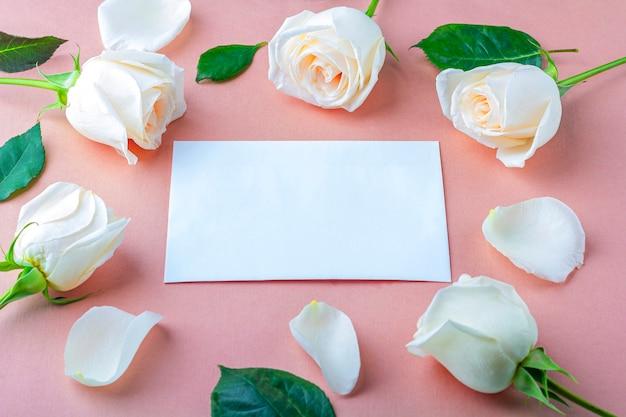 あなたのレタリングのフラット横たわっていた花の組成物。ピンクの背景に白いバラの花で作られたフレーム。招待状のグリーティングカード。