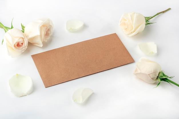 あなたのレタリングのフラット横たわっていた花の組成物。クラフト封筒と白いバラの花で作られたフレーム。招待状のグリーティングカード。トップビュー、テキストのスペースをコピー、モックアップ