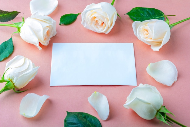 Flat lay flowers composition for your lettering. frame made of white rose flowers on pink  background. invitation greeting card.