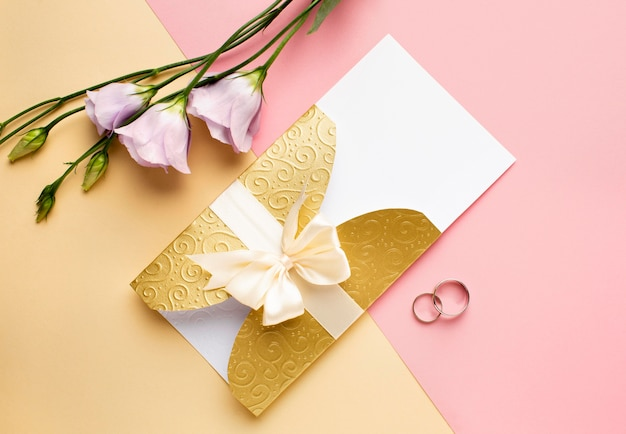 Flat lay flowers and rings luxury wedding stationery