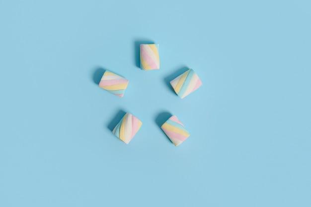 青いパステルカラーの背景に五芒星の形で配置されたカラフルなマルチカラーの甘い甘いマシュマロのフラットレイ食品組成物、広告用のコピースペース