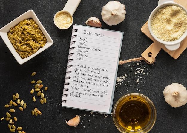 Lay piatto di ingredienti alimentari con pasta e notebook