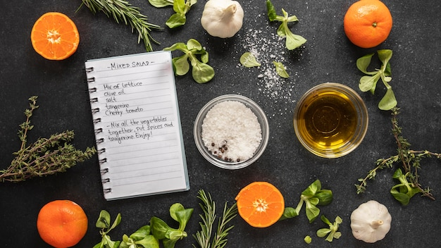Flat lay of food ingredients with herbs and notebook