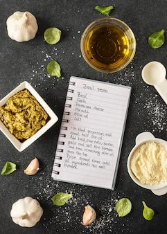 Lay piatto di ingredienti alimentari con taccuino e olio