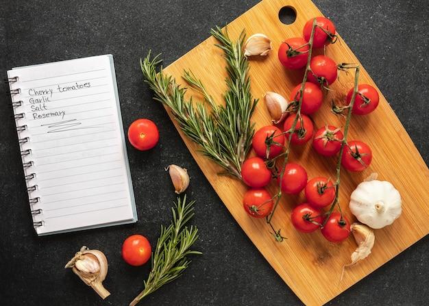 Lay piatto di ingredienti alimentari con pomodori e ricetta