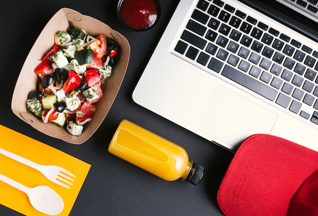 Flat lay food and laptop on black background