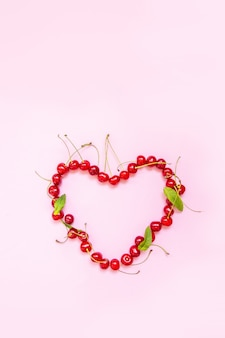Flat lay. food . red cherry berries in the shape of a heart on a pink background.