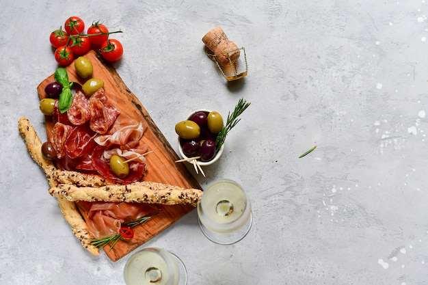 Flat lay food. traditional italian snacks for aperitif : salami, bresaola, prosciutto, olives.  and two glasses prosecco