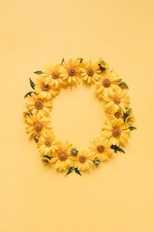 노란색 표면에 노란색 데이지 꽃으로 만든 빈 복사본 공간 모형과 평면 위치 프레임 테두리