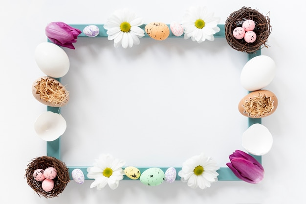 Flat lay frame made of flowers and eggs
