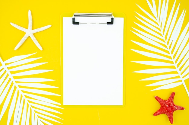 Flat lay frame summer clipboard with palm leaves and starfishes on yellow background