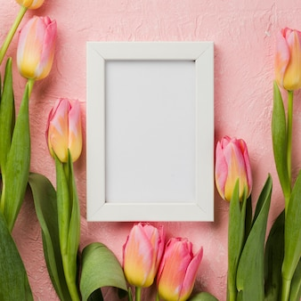 Flat lay frame and tulips on table