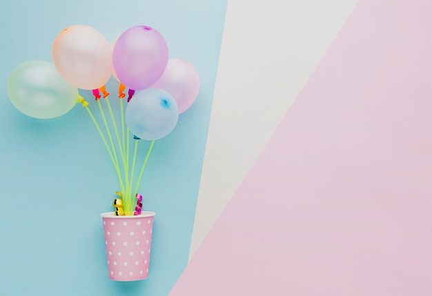 Flat lay frame with colorful balloons and cup