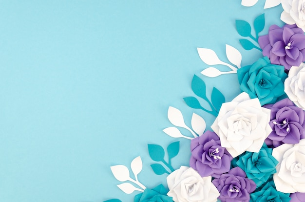 Flat lay frame with flowers and blue background