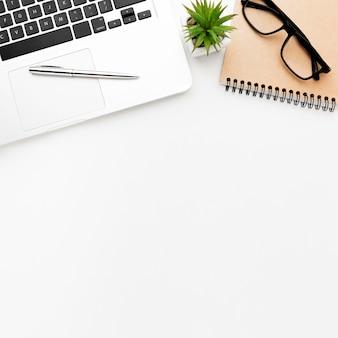 Плоская лежащая рама с очками и ноутбуком