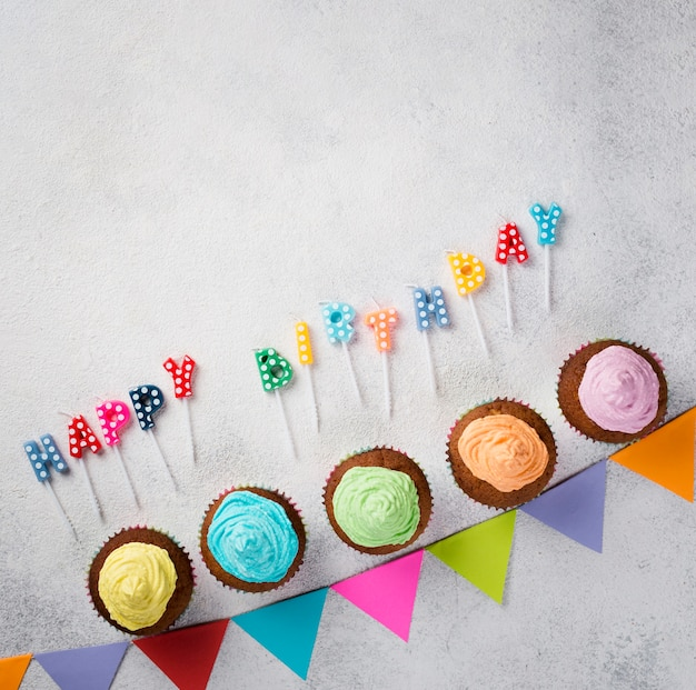 Flat lay frame with muffins and birthday candles