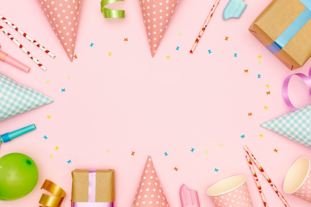 Flat lay frame with party items and pink background