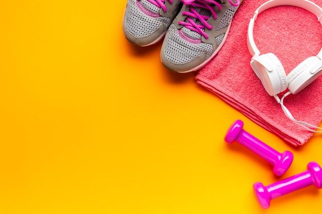 Плоская лежащая рамка с розовыми предметами на желтом фоне