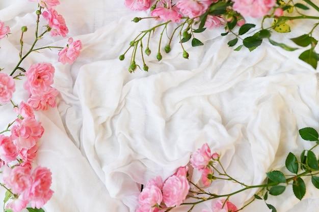 흰색 직물 배경에 분홍색 장미, 가지, 잎이 있는 평평한 프레임.