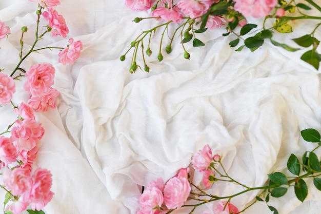 Flat lay frame with pink roses, branches, leaves on white textile background.