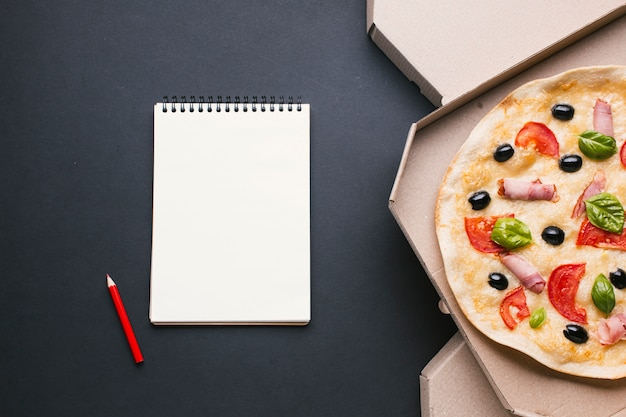 Flat lay frame with pizza and notebook