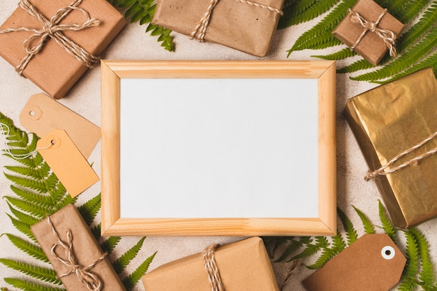 Flat lay of frame with presents and fern