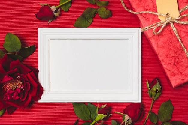Flat lay of frame with roses and present