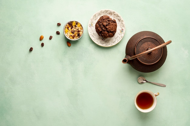 Flat lay frame with teapot and muffin