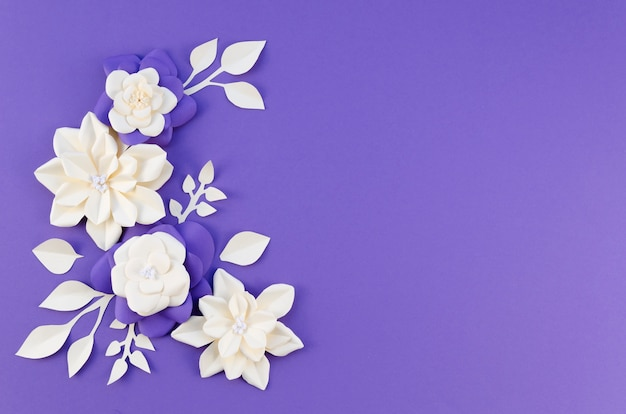 Flat lay frame with white flowers on purple background