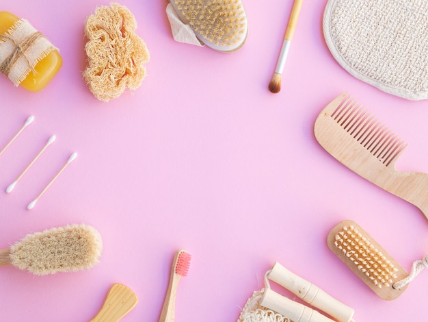 Flat lay frame with wooden items on pink background
