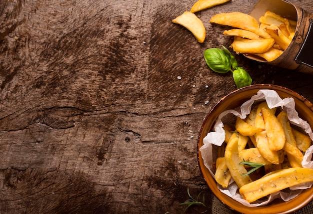 Lay piatto di patatine fritte nella ciotola con erbe aromatiche e spazio di copia