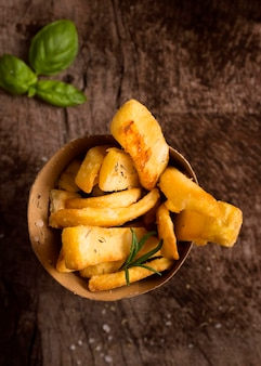 Flat lay of french fries in bowl with herbs