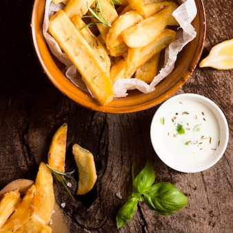 Flat lay of french fries in bowl with special sauce and herbs