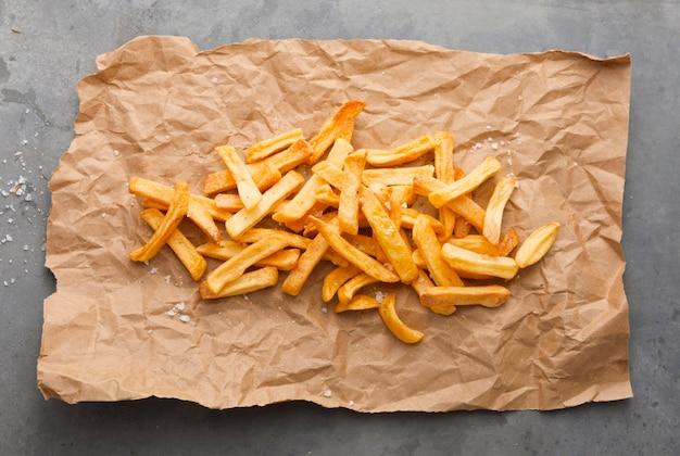 Flat lay of french fries with salt on paper