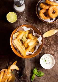 Lay piatto di patatine fritte con saliera e salsa speciale