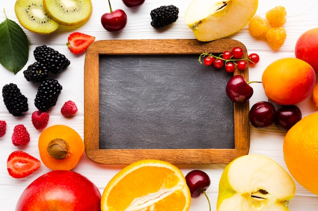 Flat-lay of fresh berries and fruits with blackboard