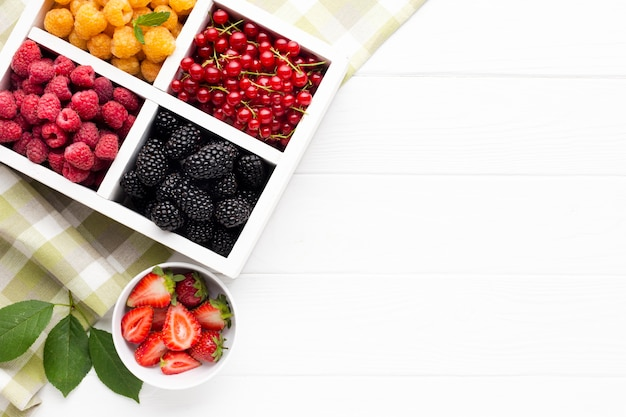 Flat-lay fresh berries and fruits with copy space