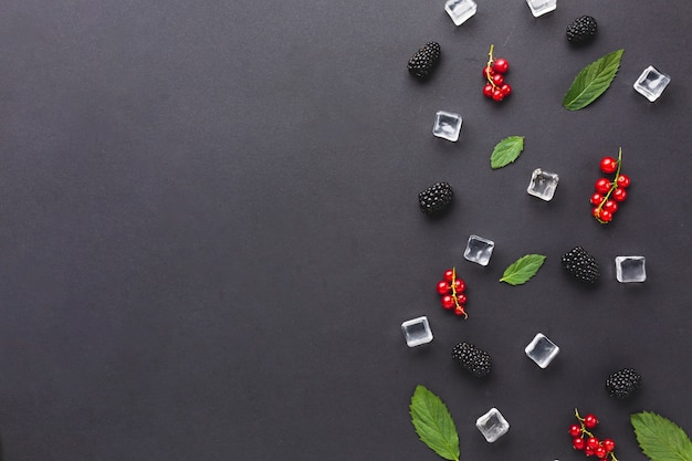 Flat-lay fresh berries and leaves with copyspace