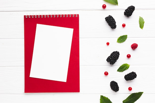 Flat-lay fresh berries with notepad