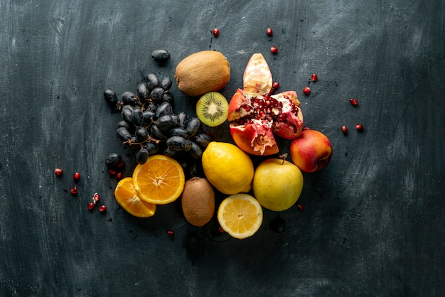 Flat lay fresh fruit selectrion layout on a grunge surface such as grapes, kiwi, orange, exotic tropical fruit