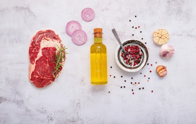 Flat lay of fresh raw beef steak with rosemary and spice on white shabby concrete background top view
