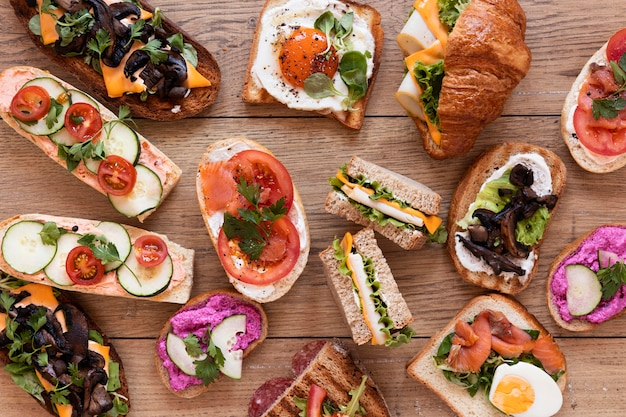 Flat lay fresh sandwiches assortment on wooden background