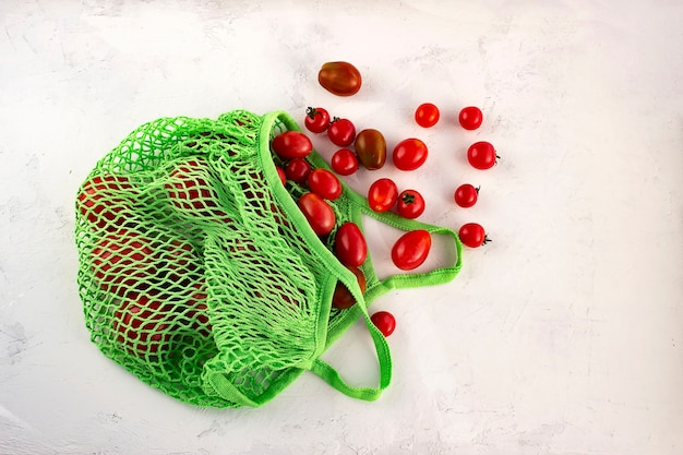 Flat lay fresh tomato in eco reusable shopping bag with net without waste on white background