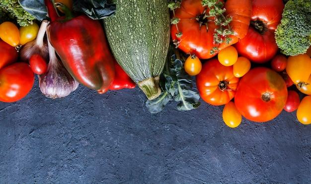 フラットは、コピースペースと暗い背景に新鮮な野菜を置きます。
